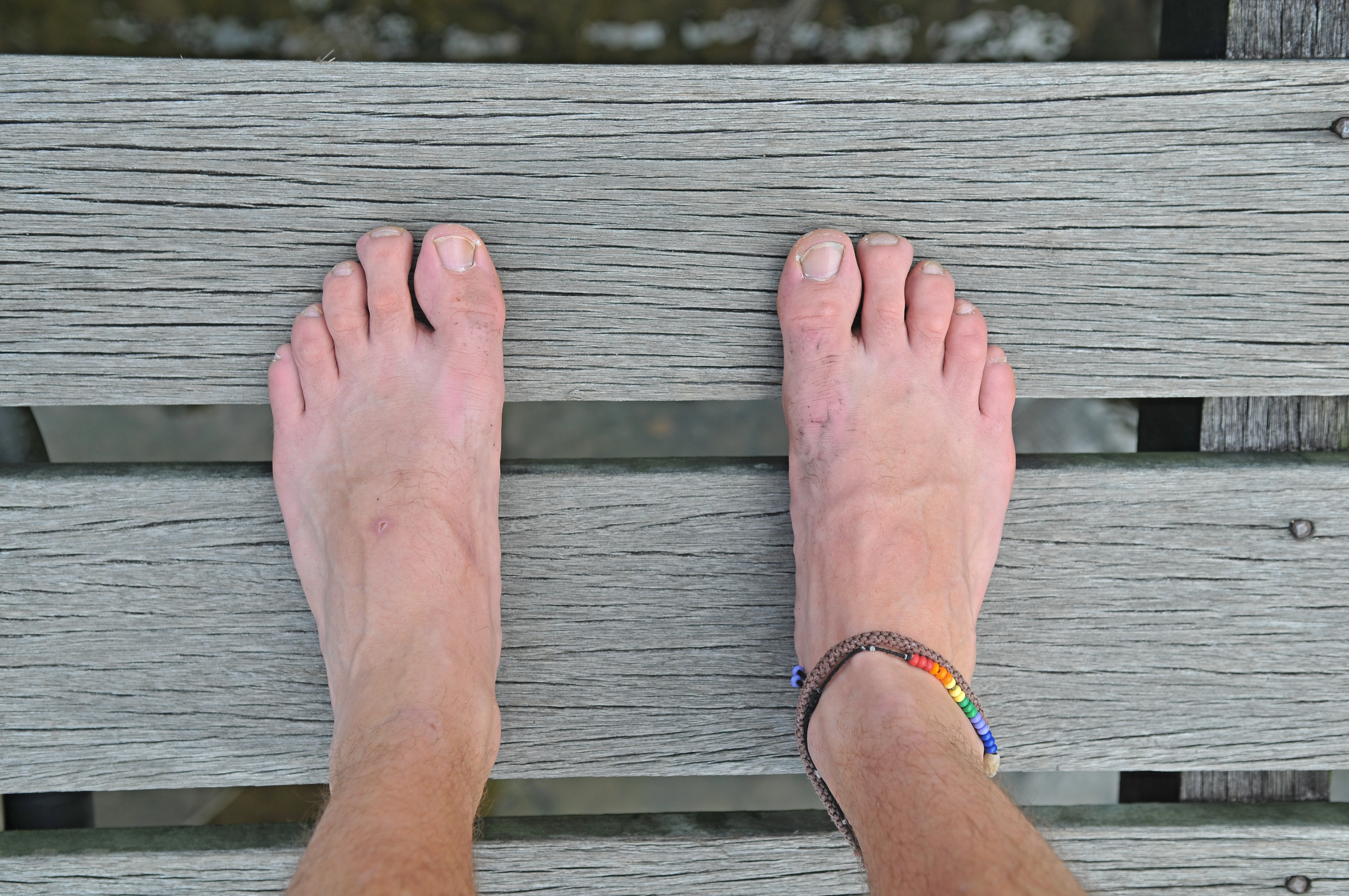 well-travelled-mans-feet-on-wood-with-friendship-anklet